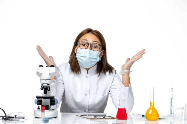 Front view female doctor in medical suit with mask due to covid posing on white space
