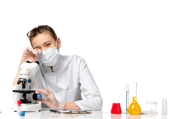 Medico femminile vista frontale in tuta medica con maschera a causa di covid utilizzando il microscopio su uno spazio bianco chiaro