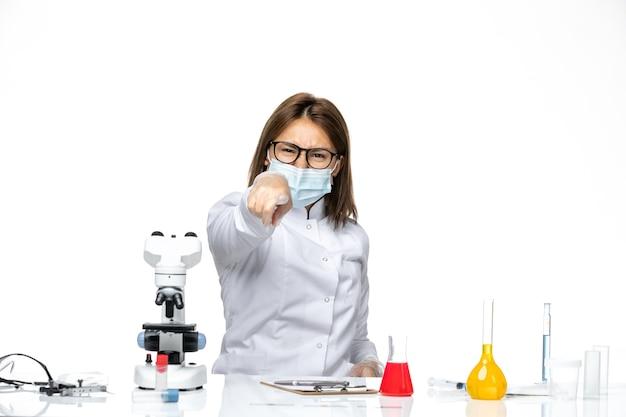 Medico femminile vista frontale in tuta medica con maschera a causa di covid su una scrivania bianca
