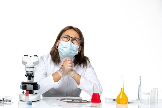 Dottoressa vista frontale in tuta medica con maschera a causa di covid lavorando e pensando su uno spazio bianco