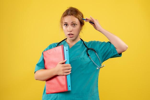 Vista frontale della dottoressa in tuta medica con documenti e analisi sulla parete gialla