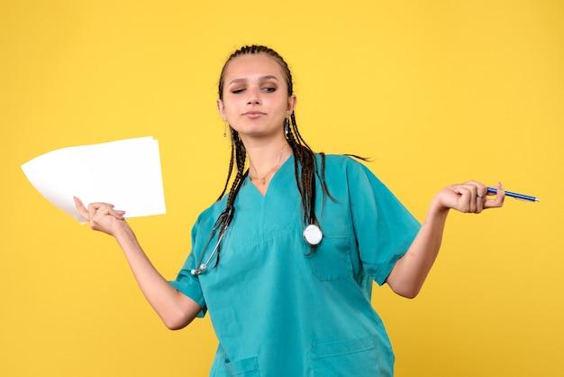 Vista frontale della dottoressa in tuta medica con documenti sulla parete gialla