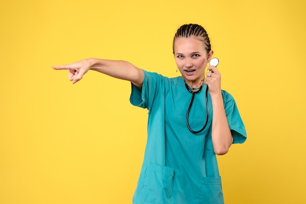 Vista frontale della dottoressa in tuta medica con lo stetoscopio sulla parete gialla