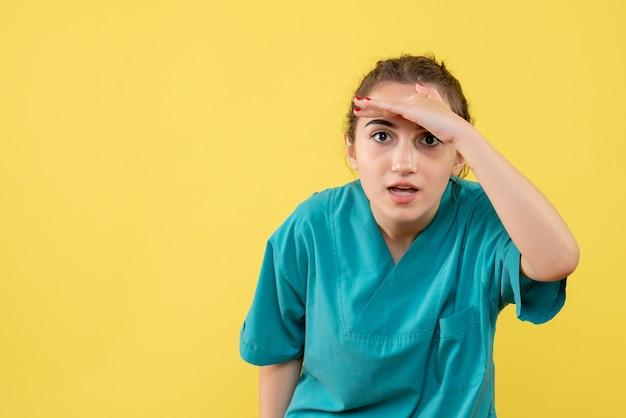 Vista frontale della dottoressa in tuta medica sulla parete gialla