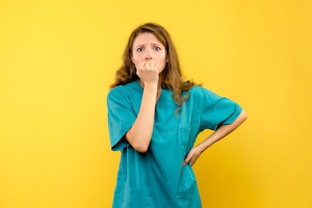 Vista frontale della dottoressa nervosa sulla parete gialla