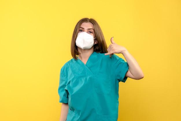 黄色い床のcovidウイルスパンデミック病院の正面図の女性医師