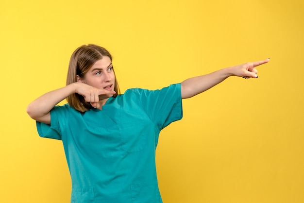 노란색 공간에 거리에서 가리키는 전면보기 여성 의사