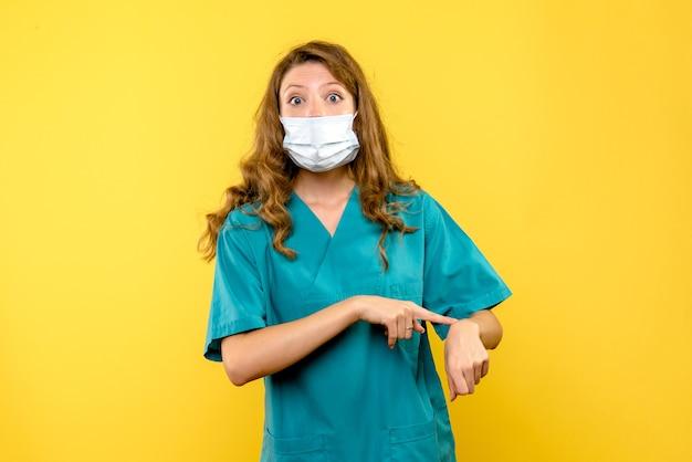 Vista frontale della dottoressa che punta al polso sulla parete gialla