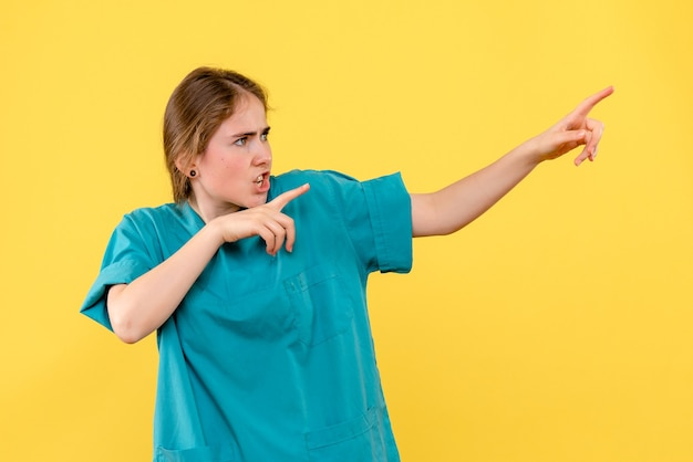 Front view female doctor pointing on yellow background health medic hospital emotion