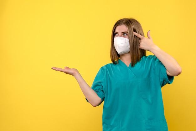 노란색 공간에 포즈 전면보기 여성 의사