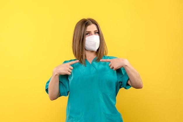 黄色い床の病院のパンデミックウイルスのマスクでポーズをとって正面図の女性医師