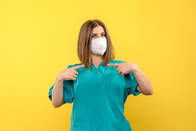 Medico femminile di vista frontale che posa con la maschera sul virus pandemico dell'ospedale del pavimento giallo