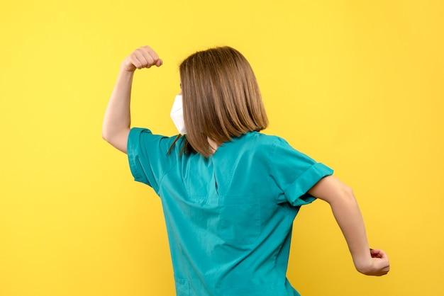 Medico femminile di vista frontale che posa con la maschera sullo spazio giallo