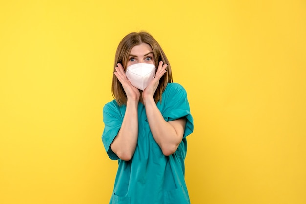 Front view female doctor posing with mask on yellow space