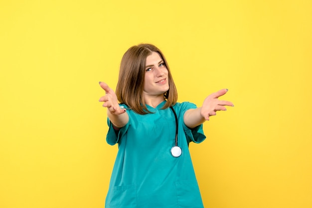 Front view female doctor posing on a yellow space