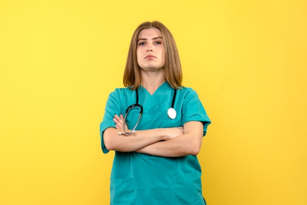 Front view female doctor posing on yellow space