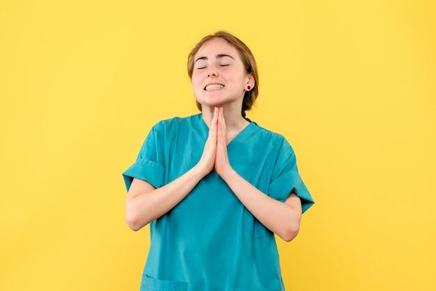Medico femminile di vista frontale che prega sull'emozione di salute del medico dell'ospedale sfondo giallo