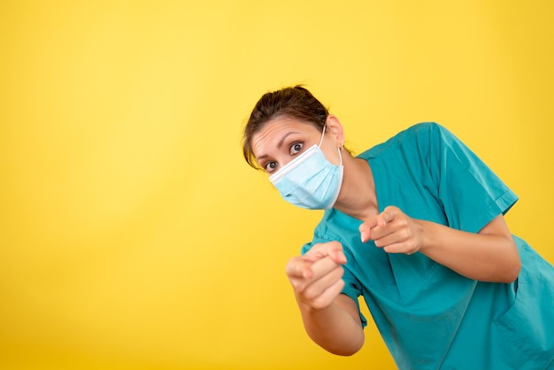 Front view female doctor in protective mask on the yellow background