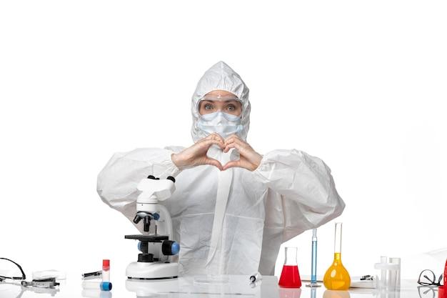 Vista frontale medico donna in tuta protettiva con maschera a causa di covid che mostra segno di amore su sfondo bianco pandemia di virus splash covid-