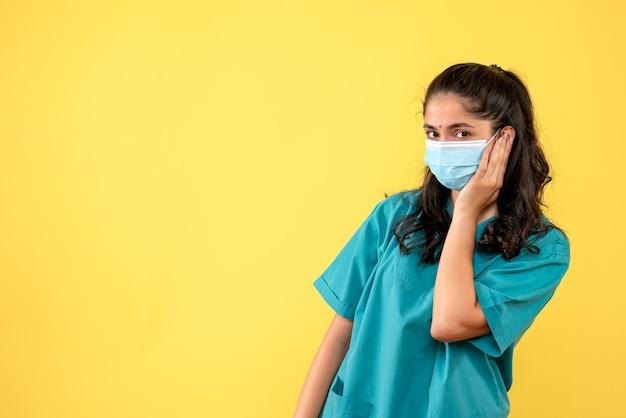 Вид спереди женщина-врач, прикладывая руку к лицу
