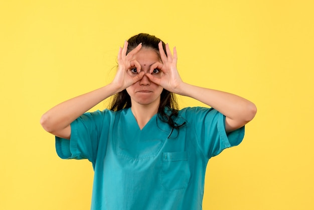 Front view female doctor putting okey sign in front of her eyes standing