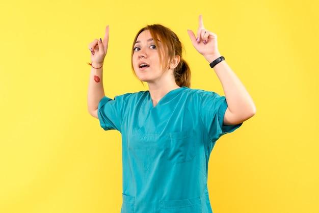 Medico femminile di vista frontale che alza le sue dita sullo spazio giallo