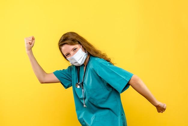 Vista frontale del medico femminile che si rallegra nella maschera sulla parete gialla