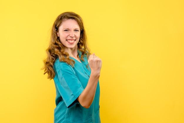 Вид спереди женщина-врач радуется на желтом пространстве