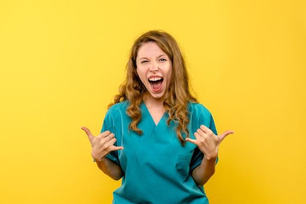 Vista frontale del medico femminile che si rallegra sulla parete gialla