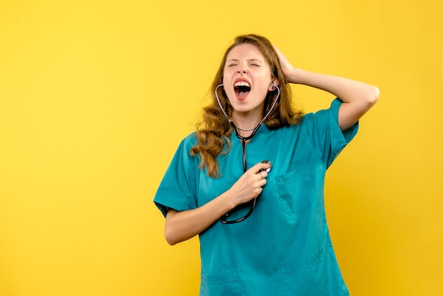 Vista frontale del medico femminile che grida sulla parete gialla