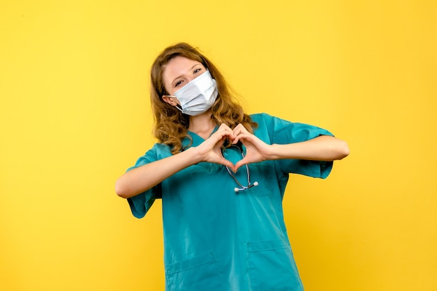 Front view of female doctor sending love in mask on yellow wall