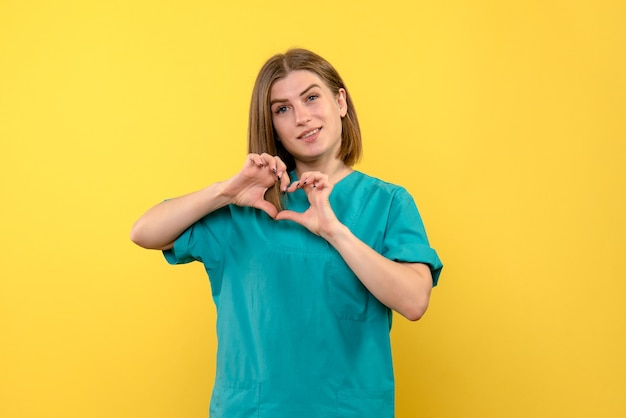 Front view female doctor sending love on yellow space