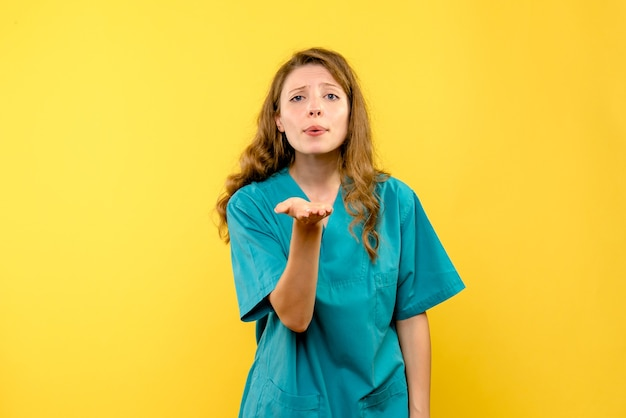 Vista frontale del medico femminile che invia amore sulla parete gialla