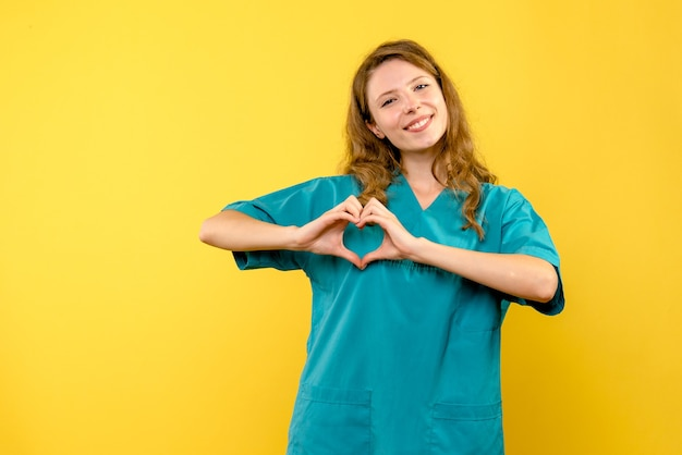 Front view of female doctor sending love on yellow wall