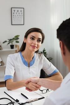 Вид спереди женщина-врач рукопожатие с пациентом
