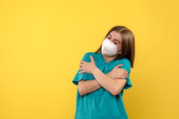 Вид спереди женщина-врач дрожит на желтом пространстве
