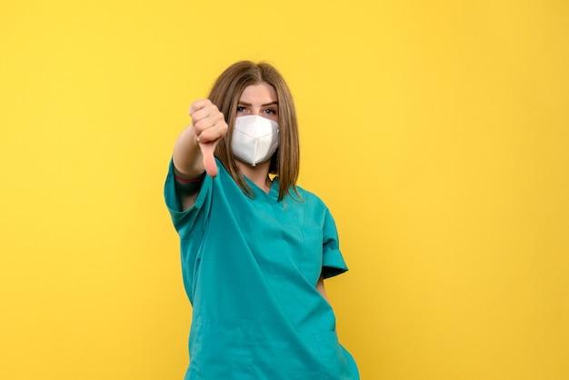 黄色のスペースに異なるサインを示す正面図の女性医師