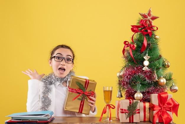 クリスマスプレゼントと黄色の背景の木の周りに座っている正面図の女性医師