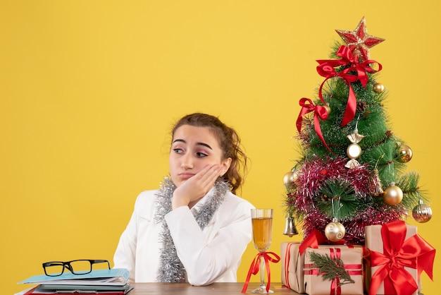 Вид спереди женщина-врач сидит вокруг рождественских подарков и грустит дерево на желтом фоне