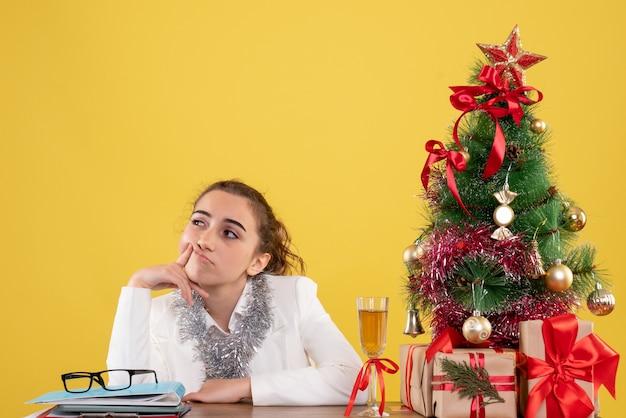 Medico femminile di vista frontale che si siede intorno ai regali di natale e all'albero annoiato