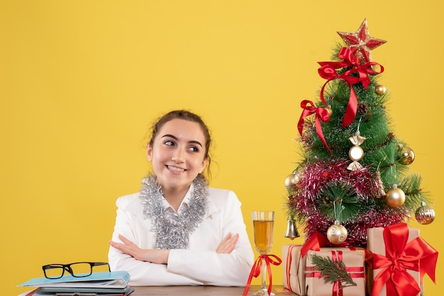 Front view female doctor sitting around christmas presents and tree on yellow background