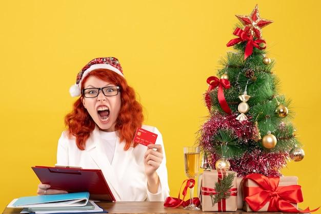 그녀의 테이블 뒤에 앉아 크리스마스 트리와 선물 상자와 노란색 책상에 은행 카드를 들고 전면보기 여성 의사