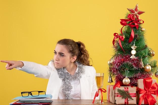 Вид спереди женщина-врач сидит за столом и указывает на желтый фон с елкой и подарочными коробками