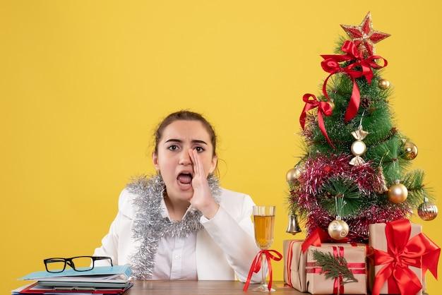 彼女のテーブルの後ろに座っている正面図の女性医師がクリスマスツリーとギフトボックスで黄色の背景を呼び出す