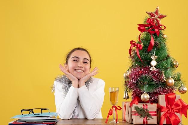 크리스마스 트리와 선물 상자와 노란색 배경에 흥분 그녀의 테이블 뒤에 앉아 전면보기 여성 의사