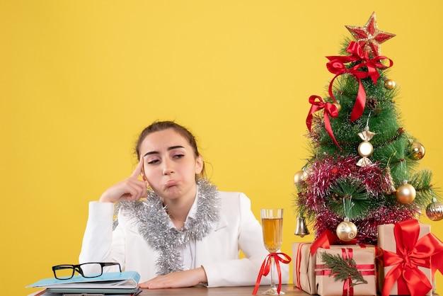Вид спереди женщина-врач сидит за столом и грустит на желтом фоне с елкой и подарочными коробками