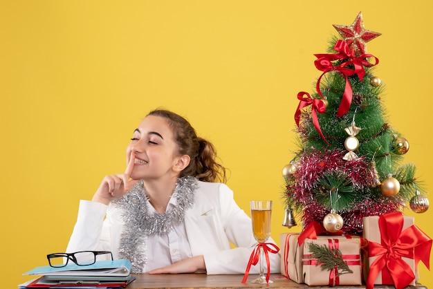 Вид спереди женщина-врач сидит за столом на желтом фоне с елкой и подарочными коробками