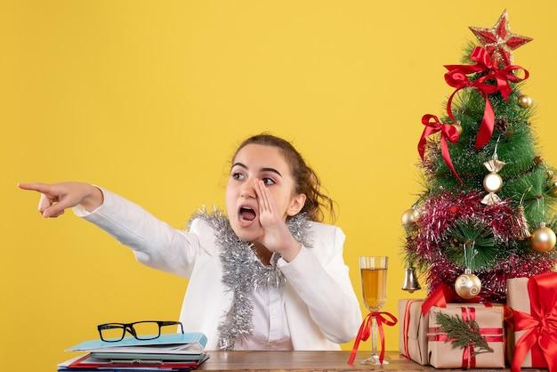 クリスマスツリーとギフトボックスと黄色の背景に彼女のテーブルの後ろに座っている正面図の女性医師