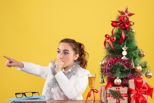 Вид спереди женщина-врач, сидящая за столом, испуганно указывая на желтый фон с елкой и подарочными коробками