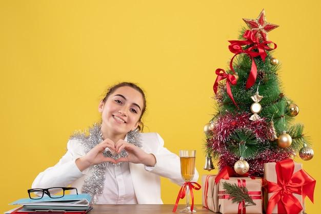 Вид спереди женщина-врач, сидящая за своим столом, отправляющая любовь на желтом фоне с елкой и подарочными коробками